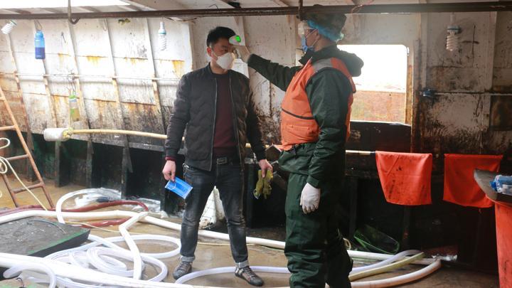 海警人员对渔民测量体温.jpg
