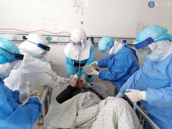李立斌(中 )戴着正压 头套,为新冠肺炎危重症病人做气管插管。.png