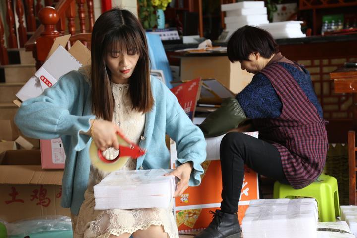 胡燕(左一)正和家人一起打包快递。见习记者 林婧 摄.jpeg