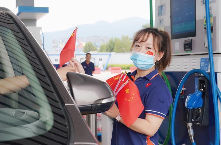 在长兴图影综合供能服务站,浙石油综合销售公司员工向进站车主发放小红旗,分享国庆喜悦。童茜 摄.jpg