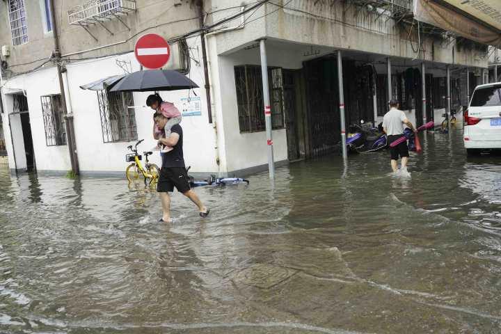 在温州市区新园觉,一父亲驮着孩子涉水出行。.jpg