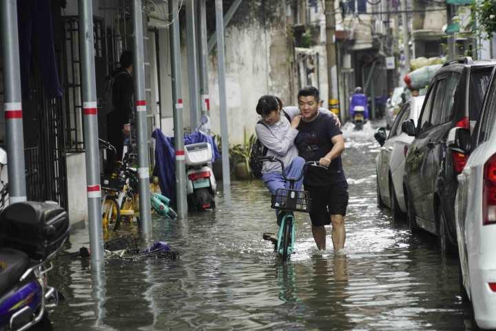 """在温州市区新园觉,一男子推车助女子过""""河""""。.jpg"""