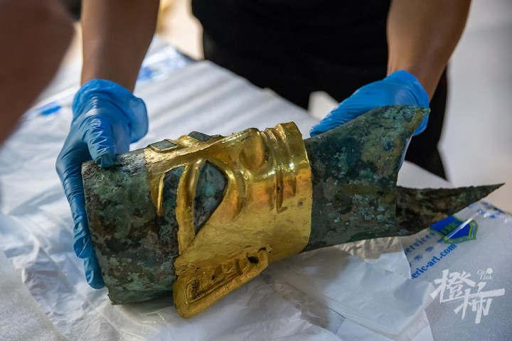 """210913czq13 浙江西湖美术馆,工作人员开箱取出展品——戴金面具的""""人头像"""",准备放入展柜,进行布展。 记者 陈中秋 摄.jpg"""